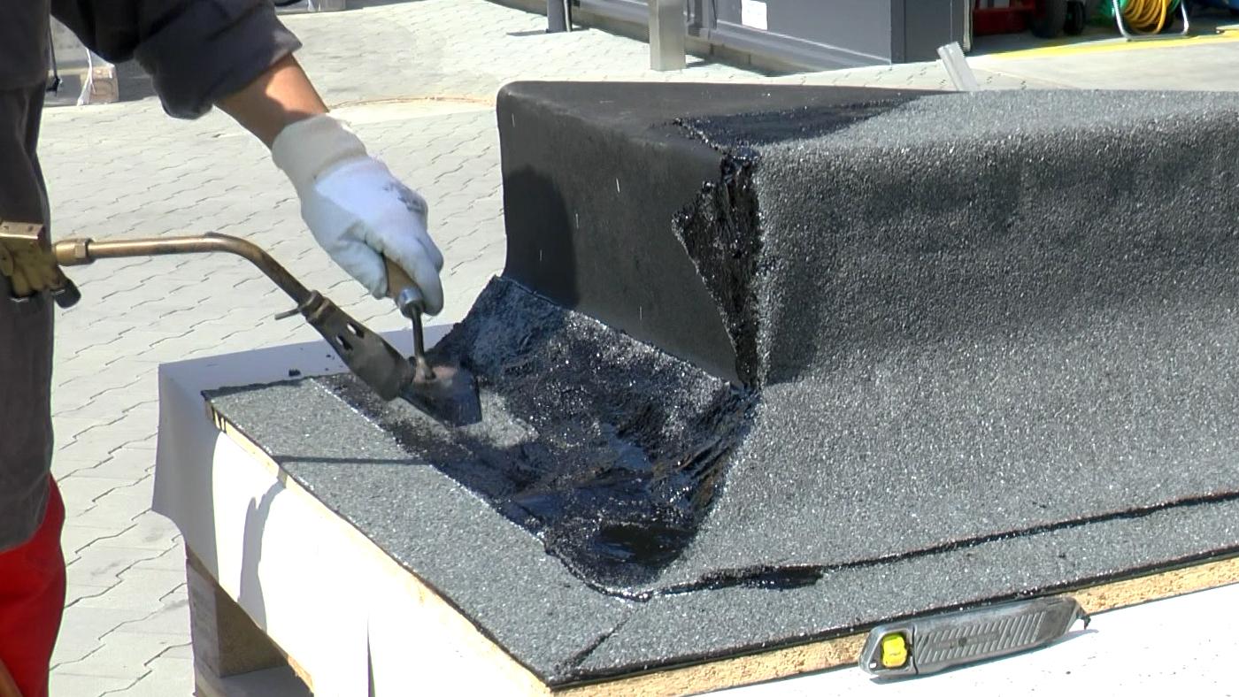 Příprava na natavení dalšího přířezu asfaltového pásu v rohu.